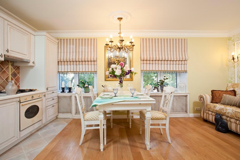 Кухонный гарнитур белого цвета. На полу паркет из натурального дерева. На потолке люстра со свечами. На окнах полосатые шторы.